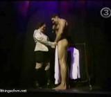 Woman helps naked man get dressed onstage