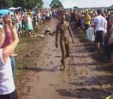 Naked mud sliding guy laughed at by crowd of girls