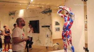 Female & male art show spectators view two naked men body painted